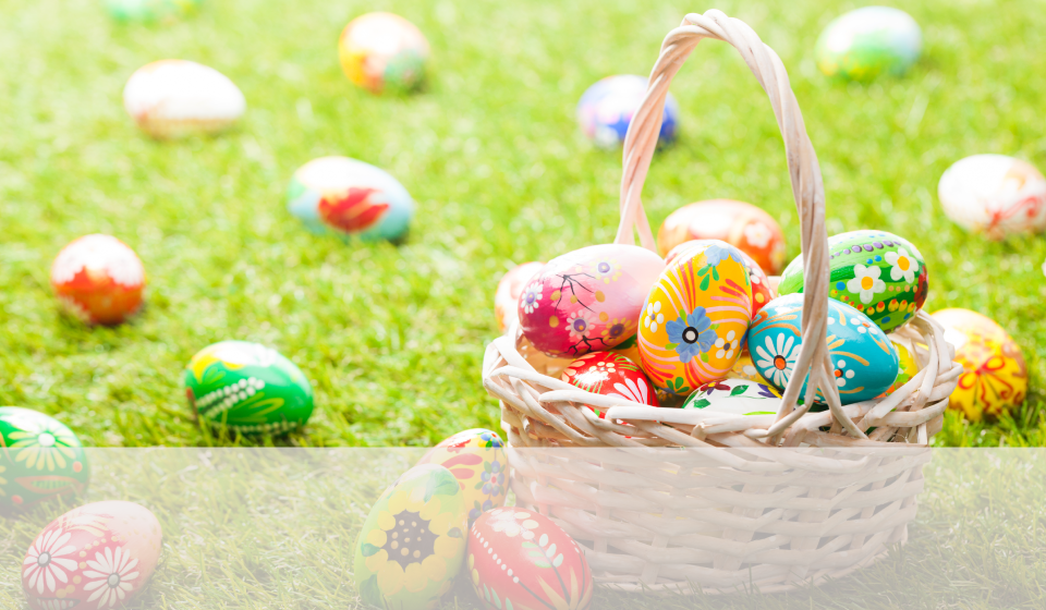 Easter egg basket filled with painted Easter eggs, with eggs spread throughout a green lawn
